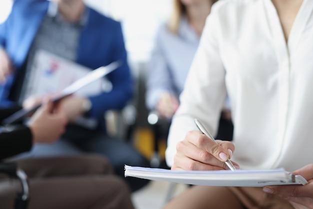 Mensen uit het bedrijfsleven voor training schrijven informatie in notitieblok