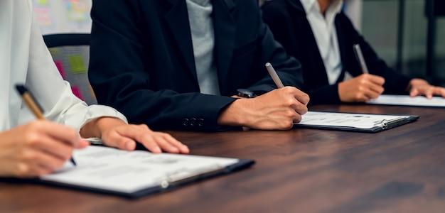 Mensen uit het bedrijfsleven vullen cv-aanvraaginformatie in op het bureau