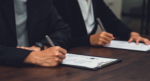 Mensen uit het bedrijfsleven vullen cv-sollicitatie-informatie op het bureau, waardoor het bedrijf het eens kan worden met de functie van de baan.