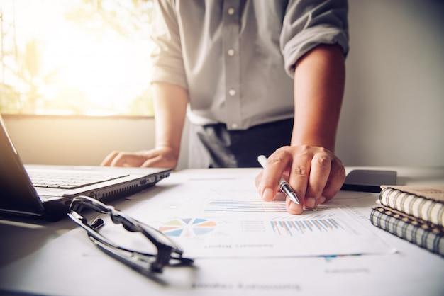 Mensen uit het bedrijfsleven werken aan accounts in bedrijfsanalyse met grafieken en documentatie.