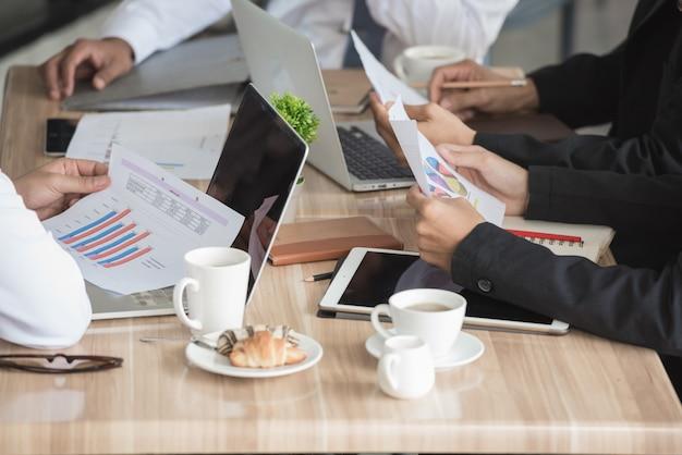 Mensen uit het bedrijfsleven werken aan de vergadertafel samen in teamwork.