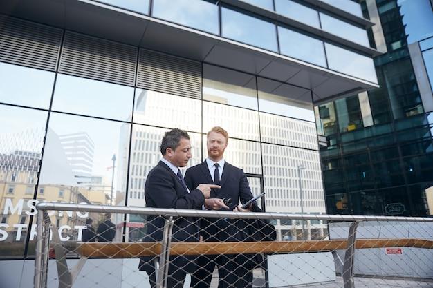 Mensen uit het bedrijfsleven werken buiten kantoorgebouw