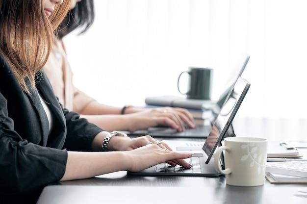 Mensen uit het bedrijfsleven werken met tabletcomputer samen in moderne kantoren
