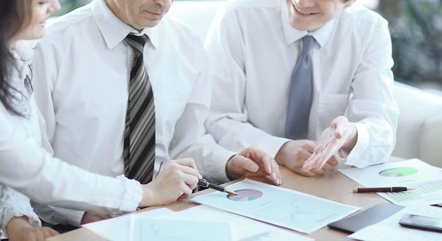 Mensen uit het bedrijfsleven werken samen en analyseren financiële cijfers op een grafiekenbedrijf