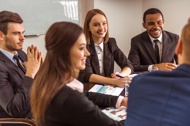Mensen uit het bedrijfsleven zitten aan een tafel en bespreken iets.