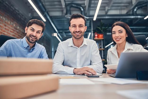 Mensen uit het bedrijfsleven zitten aan het bureau en glimlachen naar de foto front