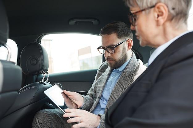 Mensen uit het bedrijfsleven zitten op de achterbank en gebruiken digitale tablet voor hun werk tijdens autorit