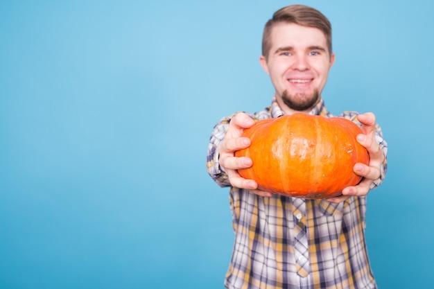 Mensen vakantie en herfst concept jonge man met pompoenen op blauwe achtergrond met kopieerruimte