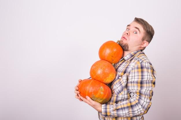 Mensen vakantie en herfst concept jonge man met pompoenen op witte achtergrond met kopie ruimte