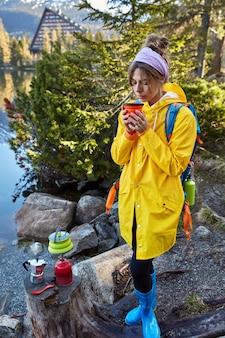 Mensen, vakantie en kamperen concept. europese vrouw ruikt aromatische koffie, houdt wegwerpbeker vast