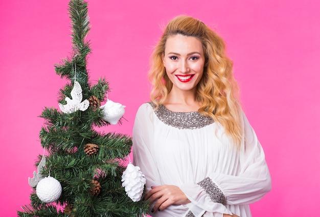Mensen, vakantie en kerstmisconcept - jonge blonde vrouw die zich dichtbij kerstboom op roze achtergrond bevindt