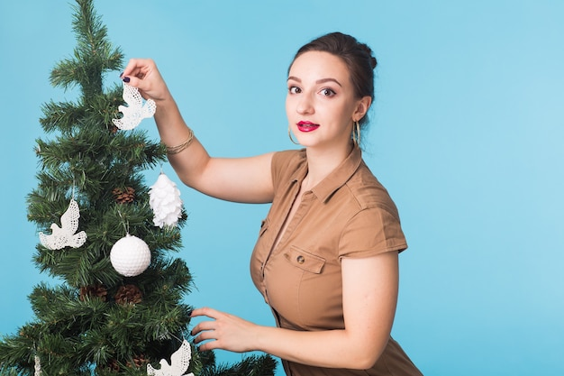 Mensen, vakantie en kerstmisconcept - vrouw die de kerstboom op blauwe muur verfraaien.