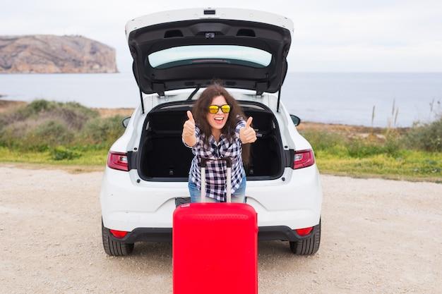 Mensen, vakantie en reisconcept - jonge vrouw met koffer die duimen in openlucht tonen.