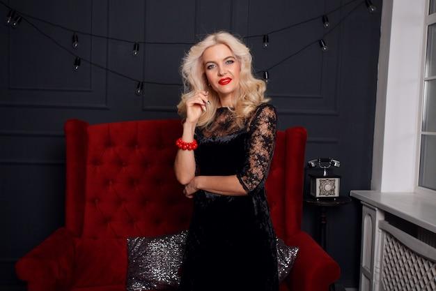 Mensen, vakantie, juwelen en luxeconcept - mooi donkerbruin, elegant vrouwenportret. retro dame met rode lippen make-up, golvend kapsel, mode edelstenen sieraden poseren modern bed in interieur