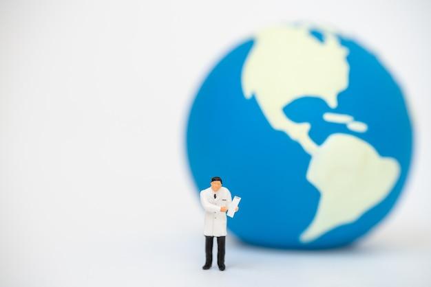 Mensen van het artsen de miniatuurcijfer met geduldig klembord die zich met miniwereldbal als achtergrond bevinden.