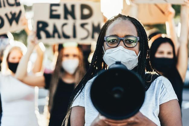Mensen van verschillende leeftijden en rassen protesteren op straat voor gelijke rechten - demonstranten die gezichtsmaskers dragen tijdens de strijd tegen het zwarte leven zijn belangrijk - focus op het gezicht van de vrouw