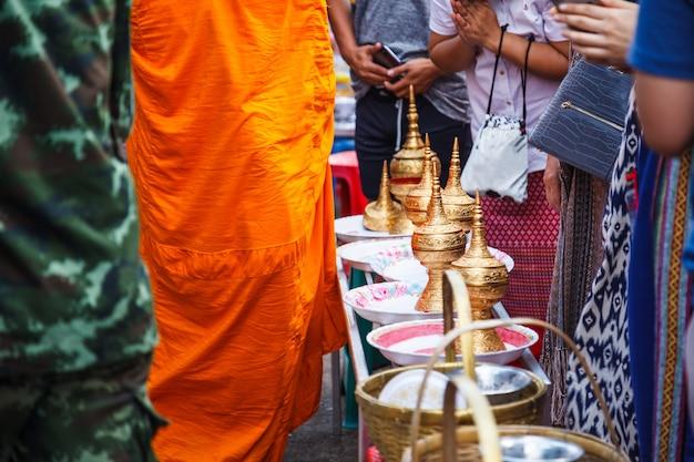 Mensen verdienen hun geld door boeddhistische monniken op dagelijkse ochtendmaaltijden voedsel te geven