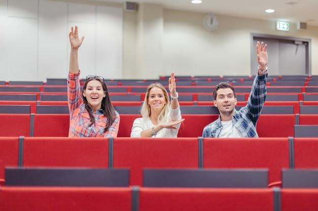 Mensen verhogen handen op seminar