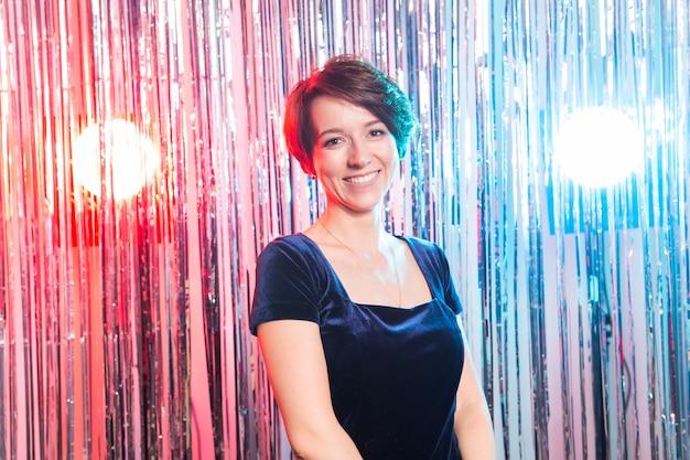 Mensen, verjaardagspartij, vakantie en glamourconcept - glimlachende vrouw in avondjurk over lichtenachtergrond