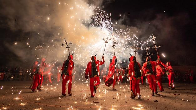 Mensen verkleed als duivels dansen met pyrotechniek