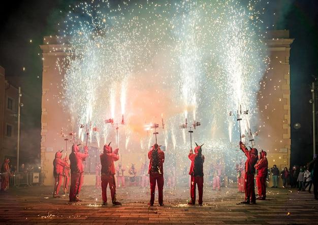Mensen verkleed als duivels die een voorstelling maakten met pyrotechniek