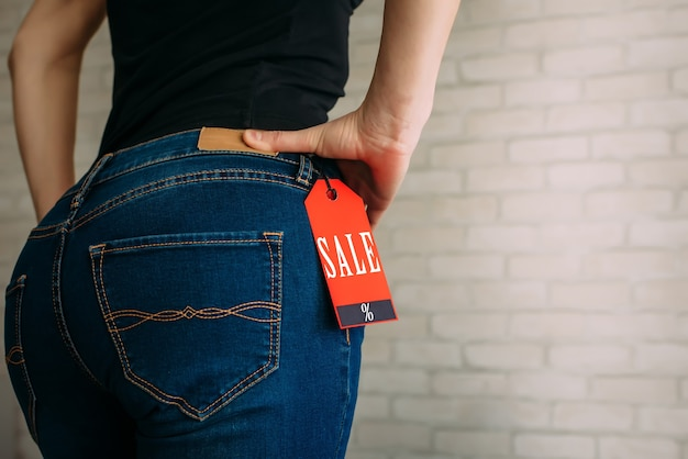 Mensen, verkoop, consumentisme concept. close-up bijgesneden foto van seksuele vrouw billen dragen blauwe casual denim broek op grijze bakstenen achtergrond in het winkelcentrum. rode tag black friday op jeans.
