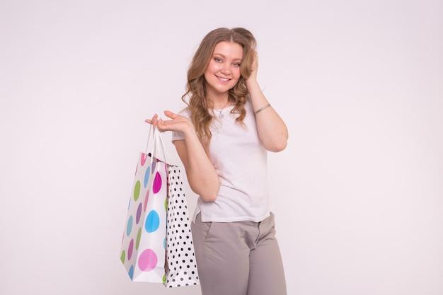 Mensen verkoop en consumentisme concept aantrekkelijke jonge vrouw gekleed in witte t-shirt en grijze broek