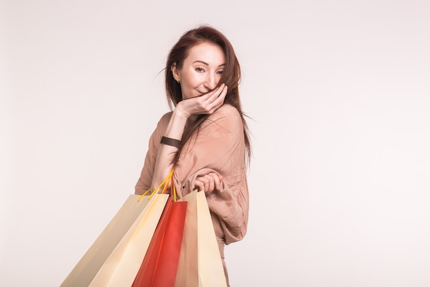 Mensen, verkoop en consumentisme concept - jonge aziatische brunette vrouw glimlachend en boodschappentassen te houden over witte muur met kopie ruimte