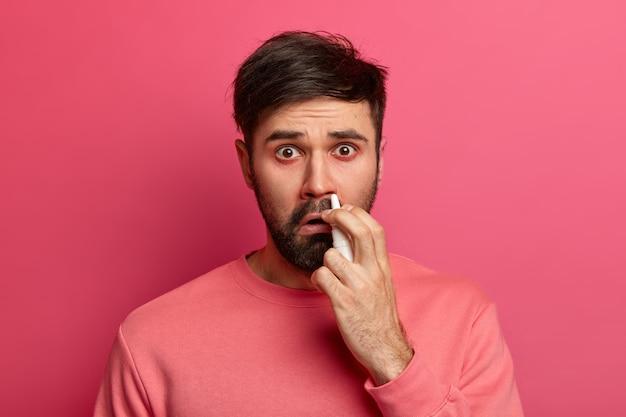 Mensen, verkoudheidssymptomen en medicatieconcept. ongelukkige zieke man gebruikt neusdruppels, heeft rhinitis en verstopte neus, geneest ziekte, lijdt aan een allergische reactie, voelt zich onwel. behandeling van sinusitis