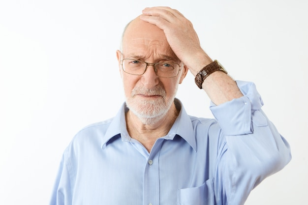 Mensen, veroudering en gezondheidsproblemen concept. gefrustreerde ongelukkige bejaarde blanke man met grijze baard die hand op zijn kale hoofd houdt met vergeetachtige gezichtsuitdrukking, lijdt aan geheugenverlies