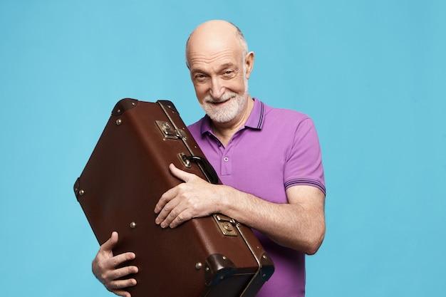 Mensen, veroudering, reizen en toerisme concept. aantrekkelijke vreugdevolle opgewonden senior man in violet t-shirt gaat vakanties doorbrengen in tropisch land, breed glimlachend, met lederen bagagezak