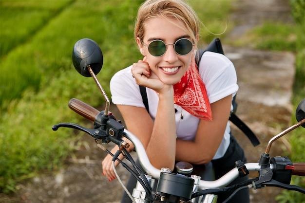 Mensen, vervoer en levensstijlconcept. gelukkig jonge blonde vrouw terloops gekleed, tevreden na een snelle rit op de motor, trendy zonnebril draagt, droomt over iets aangenaams