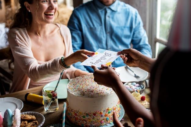 Mensen vieren verjaardagsfeest met cake en kaart
