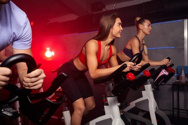 Mensen vinden het leuk om af te vallen met machine-aerobics voor een slank lichaam, op de fiets zitten, intensieve cardiotraining in de fitnessruimte, veel plezier