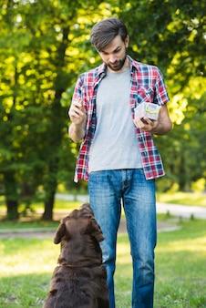 Mensen voedend voedsel aan zijn hond in tuin