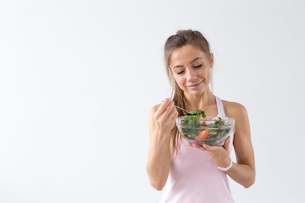 Mensen, voedsel en dieetconcept - portret van vrouw die gezond voedsel eet over wit oppervlak met exemplaarruimte.
