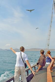 Mensen voeren meeuwen vanaf een zeilschip