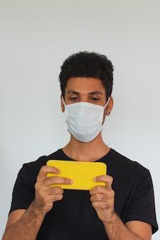Mensen volwassen zwarte dragende coronavirus de celtelefoon van de maskerholding die op wit wordt geïsoleerd