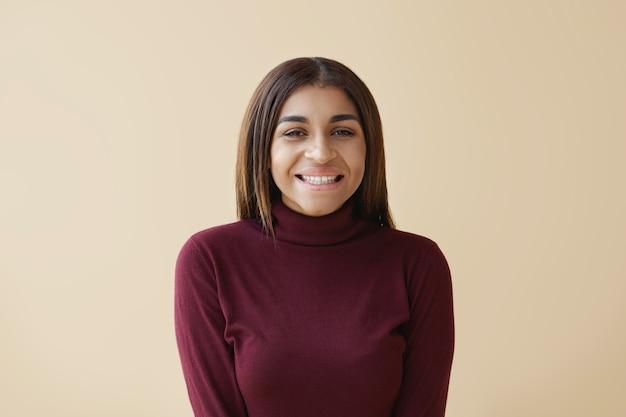 Mensen, vreugde en geluk concept. horizontale gelukkige vrolijke modieuze jonge brunette afro-amerikaanse vrouw breed grijnzend, gelukkig gevoel na goed winkelen in de uitverkoop