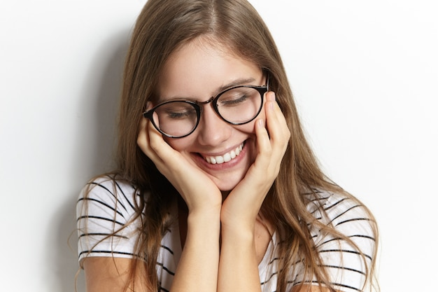 Mensen, vreugde, jeugd en geluk concept. close-up foto van charmante timide tienermeisje in stijlvolle transparante brillen verlegen naar beneden kijken en breed glimlachen, gezicht aanraken, beschaamd