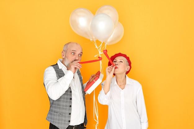 Mensen, vreugde, plezier en feestconcept. portret van elegante kale mannelijke gepensioneerde m / v en mooie rijpe vrouw genieten van verjaardagsfeestje, fluitje blazen