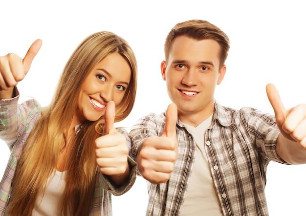 Mensen, vriendschap, liefde en vrije tijd concept - mooi paar met thumbs-up gebaar geïsoleerd op white