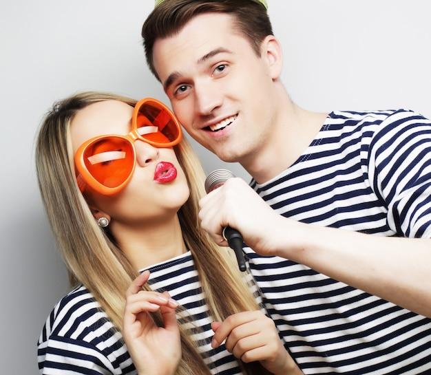 Mensen, vriendschap, liefde en vrije tijd concept - mooie jonge verliefde paar met microfoon. grote oranje glazen en kroon. klaar om te feesten.