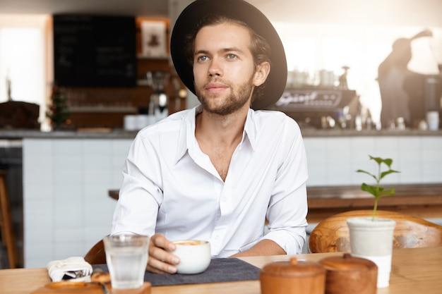 Mensen, vrije tijd en lifestyle concept. binnen schot van knappe jonge bebaarde man trendy hoed dragen aan houten tafel met mok, genieten van verse cappuccino tijdens koffiepauze, gelukkig kijken