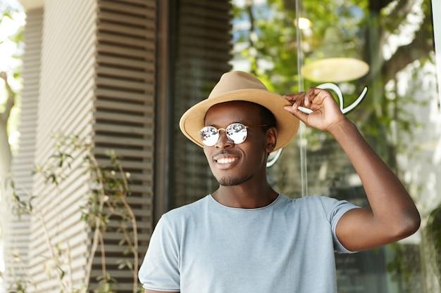 Mensen, vrije tijd en lifestyle concept. gelukkig en ontspannen jonge zwarte europese man in stijlvolle kleding aanpassen randen van zijn hoed glimlachend breed terwijl flirten met mooie vrouw in trottoir café