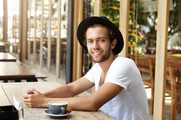 Mensen, vrije tijd en lifestyle concept. succesvolle jonge man in zwarte hoed en casual t-shirt met koffie zittend op de stoep restaurant
