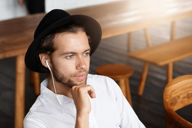 Mensen, vrije tijd en technologie concept. modieuze jongeman met baard die alleen binnenshuis ontspant, dagdroomt en naar muzieknummers op oortelefoons luistert via de online app op zijn elektronische apparaat