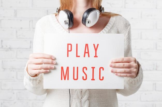 Mensen, vrije tijd en technologieconcept - gelukkige vrouw of tiener die in hoofdtelefoons aan muziek luisteren