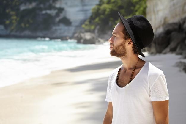 Mensen, vrije tijd, reizen en vakantie concept. stijlvolle jonge bebaarde toerist in zwarte hoed staande op zandstrand, wandelen langs de lagune en overweegt prachtig zeegezicht tijdens vakanties in de tropen