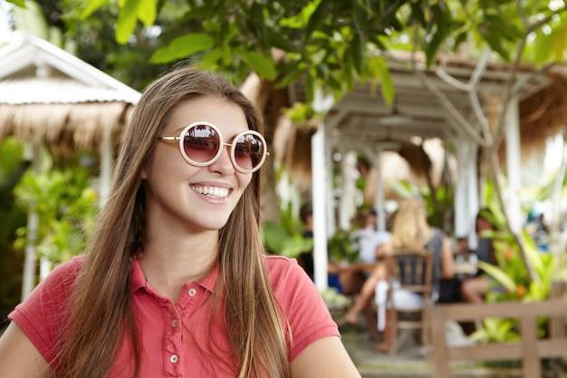 Mensen, vrije tijd, vakanties en zomerconcept. gelukkig jonge blanke zakenvrouw dragen ronde tinten ontspannen in het restaurant van het buitenhotel tijdens het ontbijt